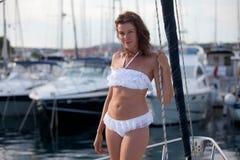 摆在航行游艇的美丽的女孩 免版税库存图片