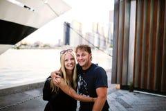 摆在船和天空前面的码头的年轻旅行的夫妇 免版税库存照片