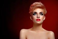 摆在艺术性的红色l的美丽的年轻白肤金发的红色有嘴妇女 免版税库存照片
