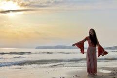 摆在英国海滩的一个时兴的夫人的剪影在日落 库存照片