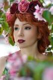 摆在苹果树的颜色的年轻美丽的女孩在春天 秀丽查出的纵向白色 图库摄影