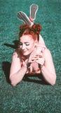 摆在草的惊人的年轻红头发人 免版税库存照片