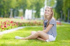 摆在草的愉快的微笑的白种人十几岁的女孩画象在绿色用花装饰的夏天公园 库存图片