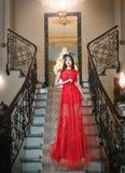 摆在葡萄酒场面的一件长的红色礼服的美丽的女孩。 免版税库存照片