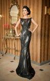 摆在葡萄酒场面的典雅的黑礼服的美丽的女孩 穿豪华礼服的年轻美丽的妇女 诱人的浅黑肤色的男人 库存图片