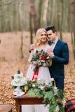 摆在葡萄酒桌附近的美好的婚礼夫妇在秋天森林里 免版税库存图片
