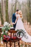 摆在葡萄酒桌附近的美好的婚礼夫妇在秋天森林里 图库摄影