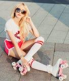 摆在葡萄酒溜冰鞋,太阳镜, T恤杉的性感的年轻愉快的妇女极好的东西微笑的夏天特写镜头画象短缺 库存图片