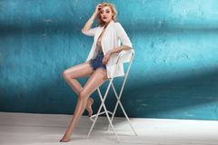 摆在蓝色墙壁上的时兴的白肤金发的女孩 图库摄影