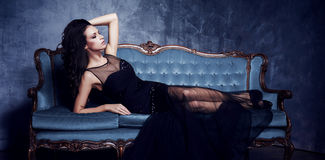 摆在蓝色沙发的黑礼服的美丽和少妇 vi 免版税库存图片