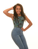 摆在蓝色牛仔裤的十几岁的女孩 免版税库存照片