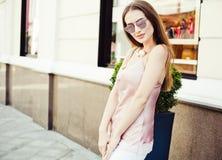 摆在街道上的太阳镜的美丽的时兴地加工好的深色头发的女孩在背景的一个夏天晚上  免版税库存图片