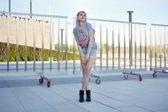 摆在街道上的时髦的迷人的少妇短小穿短的牛仔裤 库存图片