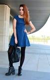 摆在街道上的美丽的少妇佩带的短上衣小点蓝色礼服 免版税图库摄影