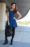 摆在街道上的美丽的少妇佩带的短上衣小点蓝色礼服 免版税库存照片