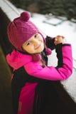 摆在街道上的逗人喜爱的微笑的女孩多雪的冬日 免版税库存图片