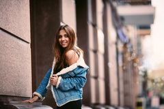 摆在街道城市的一个年轻美丽的时兴的愉快的夫人的室外画象 式样佩带的时髦的衣裳 华美的女孩 免版税库存图片