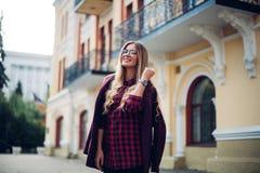摆在街道城市的一个年轻美丽的时兴的愉快的夫人的室外画象 式样佩带的时髦的衣裳 华美的女孩 库存照片