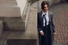 摆在街道的时尚衣裳的美丽的时髦的女人 免版税库存图片