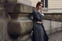 摆在街道的时尚衣裳的美丽的时髦的女人 免版税图库摄影