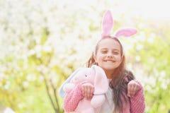 摆在象兔子的愉快的女孩在有开花的树的庭院里 免版税库存图片