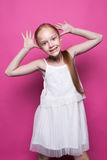 摆在象在桃红色背景的模型的白色礼服的美丽的矮小的红头发人女孩 图库摄影