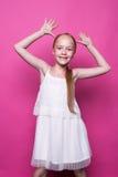 摆在象在桃红色背景的模型的白色礼服的美丽的矮小的红头发人女孩 免版税库存图片