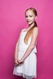 摆在象在桃红色背景的模型的白色礼服的美丽的矮小的红头发人女孩 库存图片