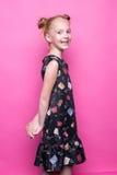 摆在象在桃红色背景的模型的礼服的美丽的矮小的红头发人女孩 免版税库存照片