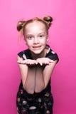 摆在象在桃红色背景的模型的礼服的美丽的矮小的红头发人女孩 库存图片
