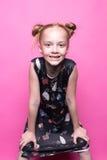 摆在象在桃红色背景的模型的礼服的美丽的矮小的红头发人女孩 库存照片