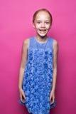 摆在象在桃红色背景的模型的蓝色礼服的美丽的矮小的红头发人女孩 库存图片