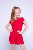 摆在象在白色背景的模型的红色礼服的美丽的矮小的红头发人女孩 免版税库存图片