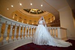 摆在豪华内部的婚礼礼服的年轻美丽的豪华妇女 有巨大的婚礼礼服的新娘在庄严庄园里 免版税库存照片