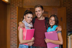 摆在走廊的三名微笑的学生 库存图片
