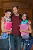 摆在走廊的三名快乐的学生 免版税库存照片