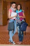 摆在走廊的两名愉快的学生 免版税图库摄影