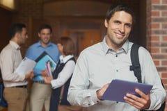 摆在走廊的美满的男性成熟学生拿着他的片剂 免版税图库摄影