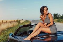 摆在路的一辆汽车附近的美丽的少妇 免版税图库摄影