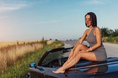 摆在路的一辆汽车附近的美丽的少妇 免版税库存照片