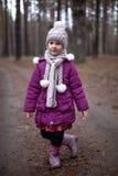 摆在路的小逗人喜爱的女孩在杉木森林里在秋天 免版税库存图片