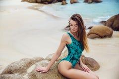 摆在转动的赃物的海滩的蓝色比基尼泳装的美丽的年轻深色的妇女显示驴子 性感的式样画象与 库存照片