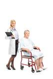 摆在轮椅的一名患者旁边的医生 库存照片