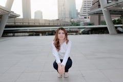 摆在边路的一个蹲位置的愉快的年轻亚裔妇女画象在都市城市背景 免版税库存图片