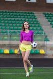 摆在运动场的年轻和美丽的健身妇女 免版税库存图片