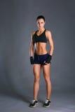 摆在运动服的肌肉少妇反对黑背景 免版税库存照片