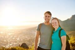 摆在远足的年轻夫妇与美丽如画的看法一起 免版税库存照片