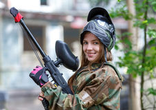 摆在迷彩漆弹运动弹药的美丽的女孩户外 图库摄影