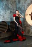 摆在透气附近的黑葡萄酒礼服的女孩用管道输送 骄傲地和周道地看在旁边 免版税图库摄影