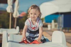 摆在逗人喜爱的白肤金发的女婴的孩子享受夏天在沙滩海边的生活时间在有五颜六色的丰足的木码头迅速增加 图库摄影